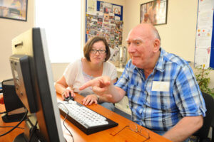 elder disabled adult child on computer accompanied by a woman