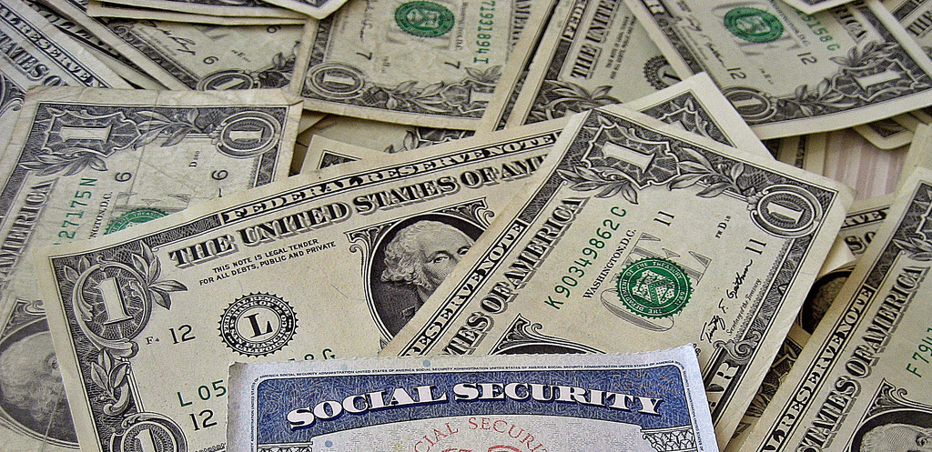 social security card on top of one dollar bills