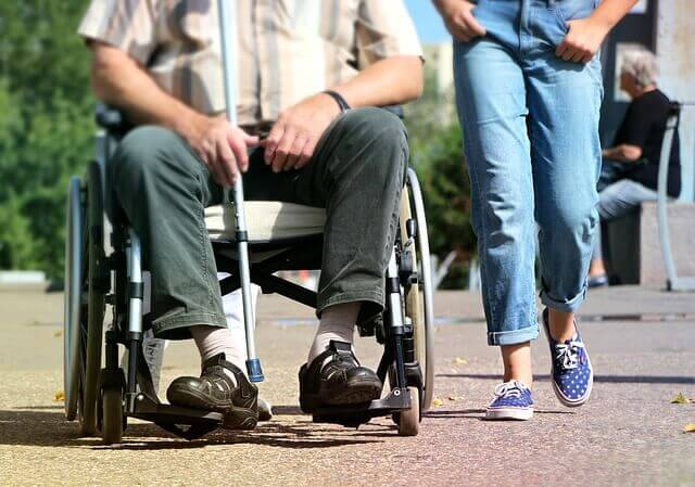 woman walking next to man in wheelchair with disability cane