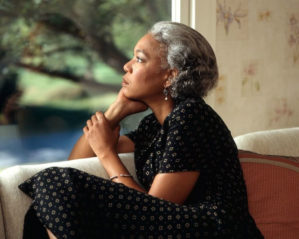 african american woman sitting on a couch looking out a window