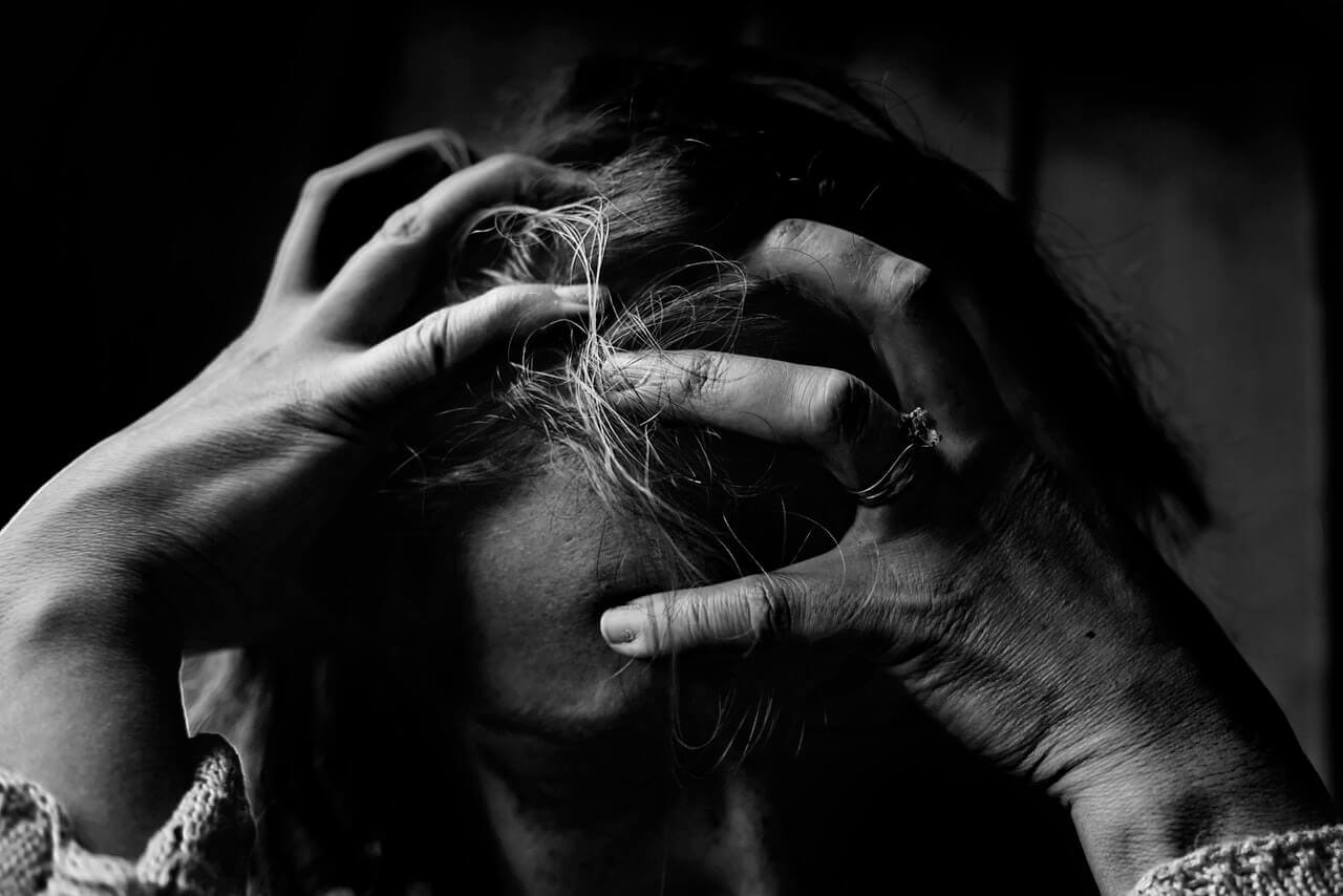 black and white photo of woman holding her head from a migraine