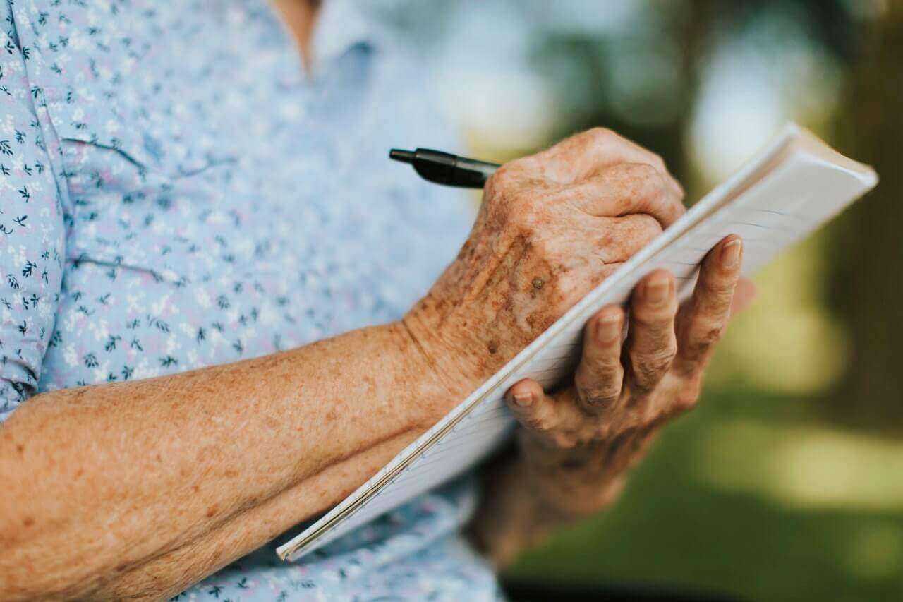 older woman writing on a notepad